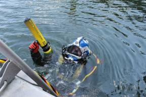A diver holding a CT-1 Probe while on the water